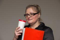 Femme d'une cinquantaine d'années d'affaires avec les verres et la serviette en cuir Image libre de droits