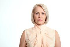 Femme d'une cinquantaine d'années d'affaires d'isolement sur le fond blanc photographie stock