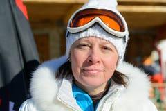 Femme d'une cinquantaine d'années dans des lunettes d'une veste blanche et de ski Image stock