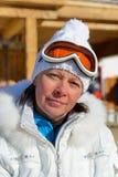 Femme d'une cinquantaine d'années dans des lunettes d'une veste blanche et de ski Images stock