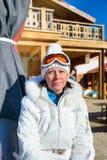 Femme d'une cinquantaine d'années dans des lunettes d'une veste blanche et de ski Photo libre de droits