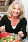 Femme d'une cinquantaine d'années en bonne santé mangeant de la salade Photo stock