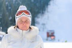 Femme d'une cinquantaine d'années en verres d'un ski de veste de blanc Images libres de droits