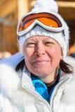 Femme d'une cinquantaine d'années en verres d'un ski de veste de blanc Images stock