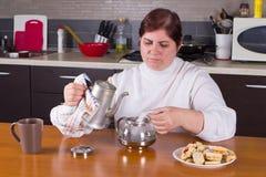Femme d'une cinquantaine d'années faisant le thé dans la cuisine Images libres de droits
