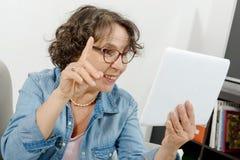 Femme d'une cinquantaine d'années faisant un appel éloigné sur l'Internet Photos libres de droits