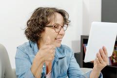 Femme d'une cinquantaine d'années faisant un appel éloigné sur l'Internet Images libres de droits