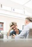 Femme d'une cinquantaine d'années heureuse à l'aide du téléphone portable avec l'homme au café de trottoir Photo stock