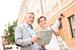 Femme d'une cinquantaine d'années montrant quelque chose équiper avec la carte de route dans la ville Images stock