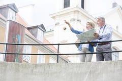 Femme d'une cinquantaine d'années montrant quelque chose équiper tout en lisant la carte par chemin de fer Images stock