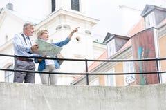 Femme d'une cinquantaine d'années montrant quelque chose équiper tout en lisant la carte par chemin de fer Image libre de droits