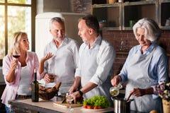 Femme d'une cinquantaine d'années racontant des histoires aux amis pluss âgé tout en faisant cuire le déjeuner Photographie stock libre de droits