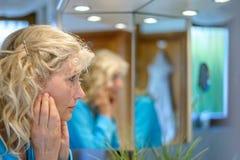 Femme d'une cinquantaine d'années regardant elle-même dans un miroir photo stock