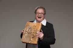 Femme d'une cinquantaine d'années riante d'affaires en verres avec du Br en cuir Image libre de droits