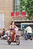 Femme d'une cinquantaine d'années sur l'e-vélo au centre de la ville, Nanjing, Chine Photos libres de droits