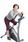Femme, d'une cinquantaine d'années sur un vélo stationnaire. Image stock