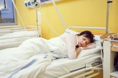 Femme d'une cinquantaine d'années triste se situant dans l'hôpital Image stock