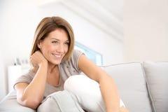Femme d'une cinquantaine d'années de sourire dans le sofa Photographie stock libre de droits