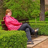 Femme d'une cinquantaine d'années détendant sur un banc de parc Image stock