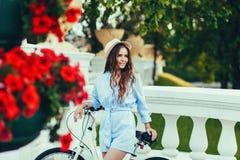Femme d'une manière élégante habillée dans le chapeau avec la bicyclette photo stock