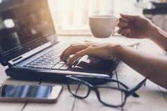 Femme dactylographiant sur l'ordinateur portable sur le lieu de travail dans le siège social Image stock