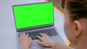 Femme dactylographiant sur le clavier d'ordinateur portable avec l'?cran vert vide en caf? clips vidéos