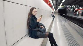 Femme dactylographiant sur le smartphone à la station de métro Train de attente banque de vidéos