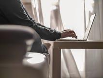 Femme dactylographiant sur un ordinateur portable tout en se reposant sur un sofa dans la perspective d'une fenêtre photos libres de droits