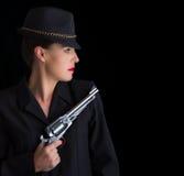 Femme dangereuse dans le noir avec le pistolet argenté Photos stock