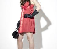 Femme dans de robe les gants et le sac à main rouges en arrière Images stock