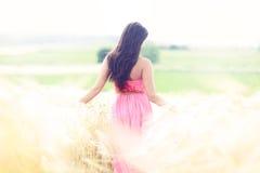 Femme dans des domaines de ciel d'or Photos stock