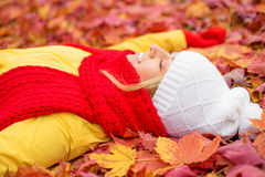 Femme dans des feuilles rouges appréciant le temps Images libres de droits