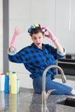 Femme DANS des gants d'un nettoyage se reposant sur un plan de travail de cuisine photo libre de droits