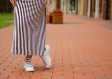 Femme dans des jambes femelles de robe dans des espadrilles de rue sur la mode de beauté de fond de tache floue Photographie stock libre de droits