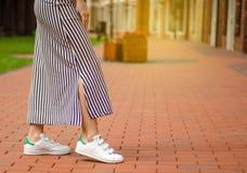 Femme dans des jambes femelles de robe dans des espadrilles de rue sur la mode de beauté de fond de tache floue Photos libres de droits
