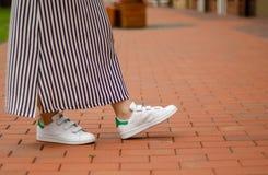 Femme dans des jambes femelles de robe dans des espadrilles de rue sur la mode de beauté de fond de tache floue Photographie stock