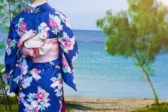 Femme dans des kimonos japonais traditionnels marchant à la plage photo libre de droits