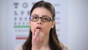 Femme dans des lunettes appliquant le baume à lèvres et souriant à la caméra, dame sûre banque de vidéos