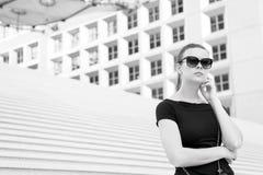 Femme dans des lunettes de soleil posant sur des escaliers et construisant dans les Frances photo stock