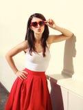 Femme dans des lunettes de soleil rouges soufflant le baiser de lèvres Photo stock