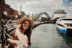 Femme dans des lunettes de soleil tenant la main d'ami, tout en prenant une photo de elle, en Sydney Harbour Photographie stock libre de droits