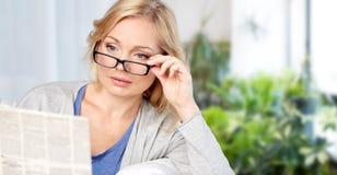 Femme dans des lunettes lisant le journal ? la maison photos stock