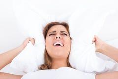 Femme dans des oreilles de bâche de lit avec l'oreiller en raison du bruit photos stock