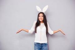 Femme dans des oreilles de lapin gesticulant ses épaules Image stock