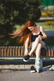 Femme dans des patins de rouleau se reposant sur le banc photos libres de droits