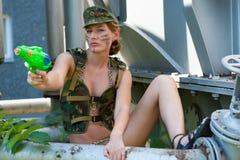Femme dans des pousses de camouflage d'un pistolet d'eau Photo libre de droits