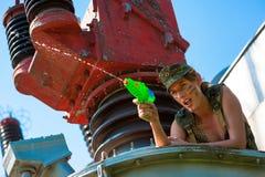 Femme dans des pousses de camouflage d'un pistolet d'eau Photos libres de droits