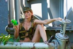 Femme dans des pousses de camouflage d'un pistolet d'eau Photographie stock libre de droits