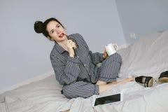 Femme dans des pyjamas tenant la tasse de café sur son lit Images stock