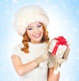 Femme dans des vêtements d'hiver tenant un présent Images libres de droits